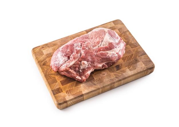Carne cruda del collo di maiale sul bordo del macellaio isolato su fondo bianco.