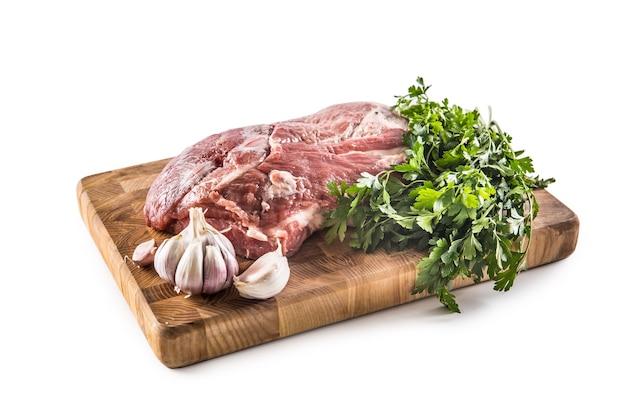 Carne cruda del collo di maiale con i pomodori ed il rosmarino delle erbe del prezzemolo dell'aglio sul bordo del macellaio isolato su fondo bianco.