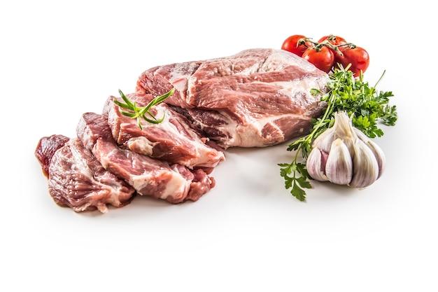 Carne cruda di collo di maiale con aglio prezzemolo erbe pomodori e rosmarino isolati su sfondo bianco.