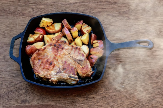 Bistecca di maiale con patate su una patata di cipolla bianca rurale nel villaggio