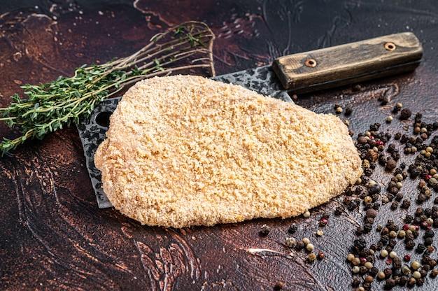 Scaloppa di maiale cruda o cotoletta su una mannaia con erbe aromatiche. sfondo scuro. vista dall'alto.