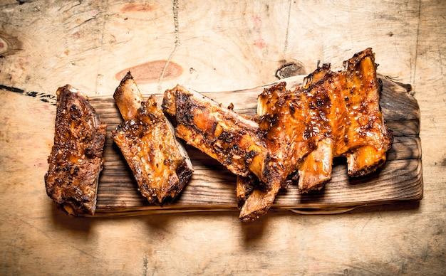 Costine di maiale alla griglia sulla vecchia scheda sulla tavola di legno.