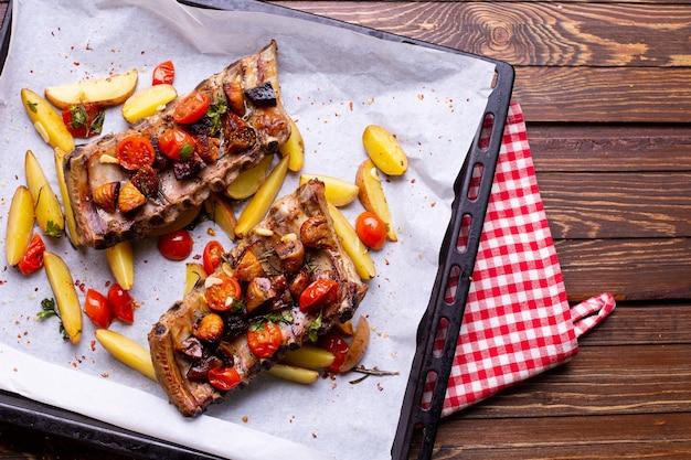 Costine di maiale con verdure su uno sfondo di legno