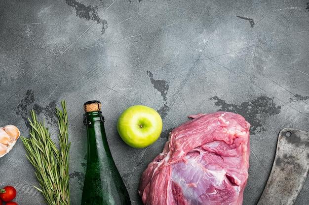 Set di ingredienti per arrosto di maiale, con sidro secco di mele, su sfondo di tavolo in pietra grigia, vista dall'alto piatta, con spazio di copia per il testo
