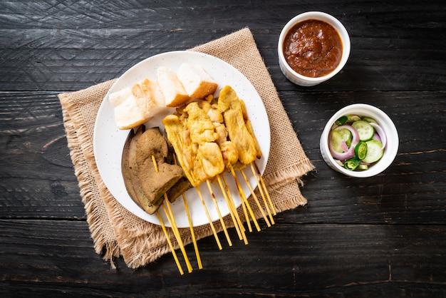 Maiale satay e fegato satay con pane e salsa di arachidi e sottaceti che sono fette di cetriolo e cipolle in aceto, stile asiatico