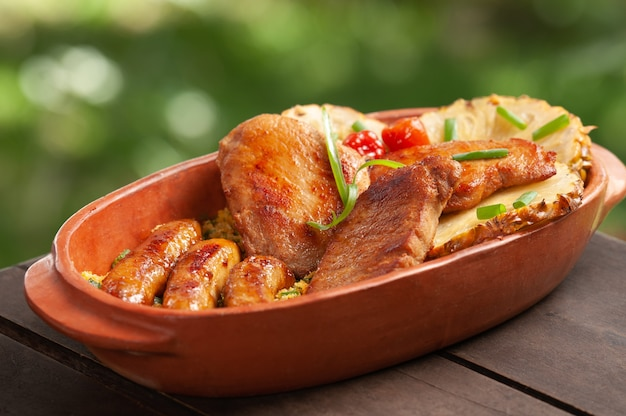 Maiale e salsiccia nella ciotola di argilla accompagnati da fette di ananas cibo brasiliano