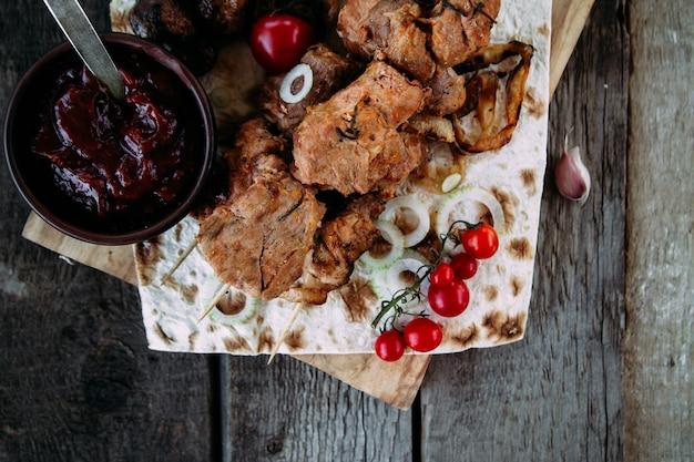 Spiedini di carne di maiale con verdure e salsa di pomodoro su un tavolo di legno