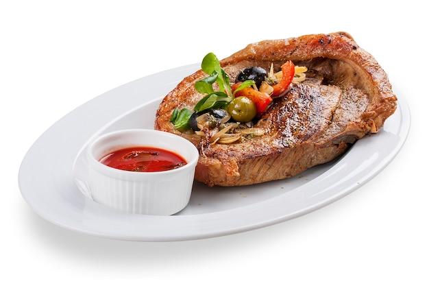 Bistecca di maiale alla greca. su uno sfondo bianco