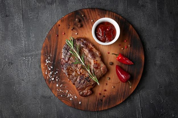Bistecca di maiale con salsa barbecue. guarnire con un rametto di rosmarino, peperoncino, sale grosso e pimento. su una tavola di legno rotonda. vista dall'alto. sfondo grigio cemento.