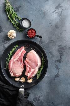 Bistecche di maiale, filetti per grigliare, cottura in padella padella nera con erbe aromatiche, spezie vista dall'alto spazio flatlay per il testo. verticale.
