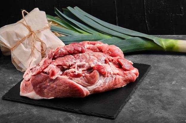 Filetto di maiale, carne fresca su un piatto di ardesia su uno sfondo grigio con verdure.