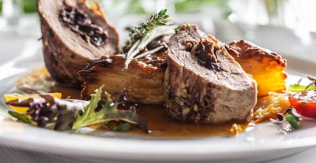 Filetto di maiale ripieno di prugne, riduzione al vino rosso con patate gratinate. piatto principale festivo creativo servito a un matrimonio o altra celebrazione.