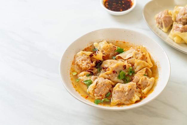 Zuppa di wonton di maiale o zuppa di gnocchi di maiale con peperoncino arrosto - stile asiatico