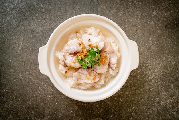 Zuppa di porridge o riso bollito con scodella di pesce