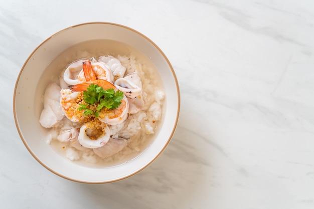 Zuppa di porridge o riso bollito con ciotola di frutti di mare (gamberetti, calamari e pesce)