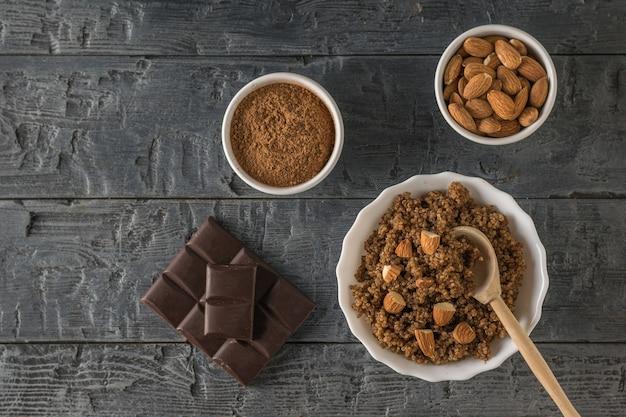 Porridge, quinoa, cacao, cioccolato e mandorle su un tavolo di legno. dieta sana. disposizione piatta.
