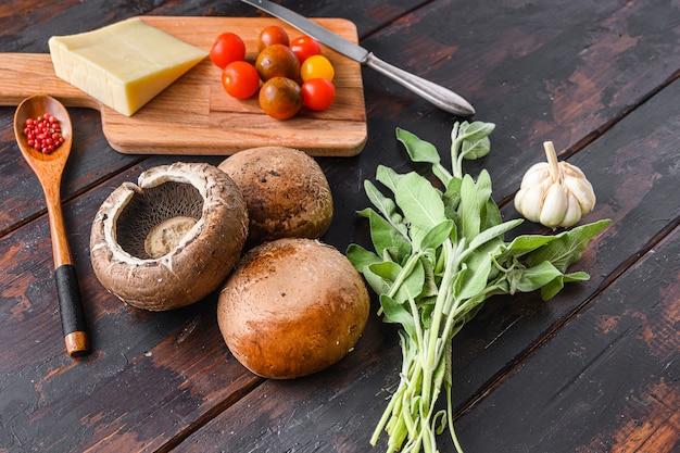 Funghi portabello ingredienti per la cottura, formaggio cheddar, pomodorini e salvia