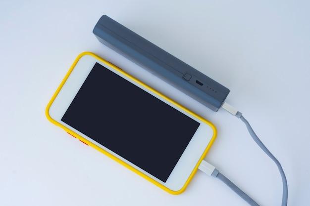 Il caricabatterie portatile carica uno smartphone isolato su uno sfondo bianco. mockup di telefono cellulare con schermo bianco e power bank.