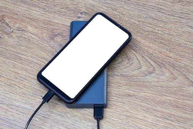 Il caricabatterie portatile carica uno smartphone su un tavolo di legno. mockup di telefono cellulare con schermo bianco e power bank.