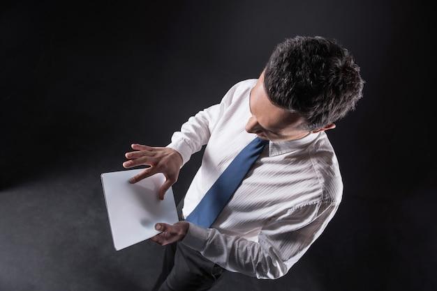 Dispositivo portatile. vista dall'alto di un bell'uomo bello in piedi e lavorando sul tablet mentre lo tiene tra le mani