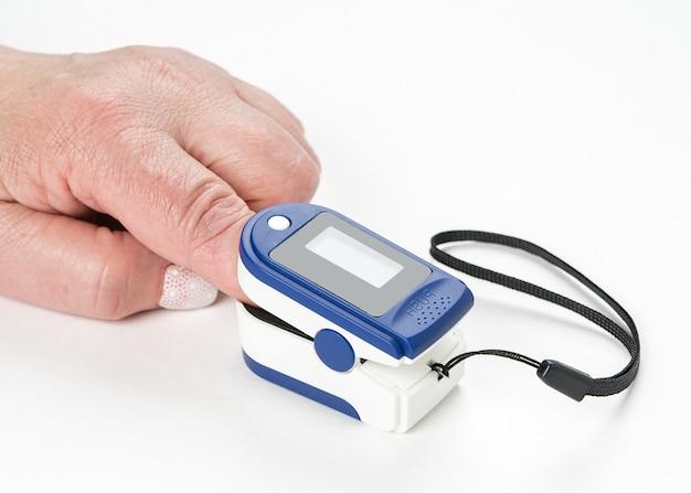 Pulsossimetro digitale portatile da dito sulla mano di una donna isolata sul muro bianco.
