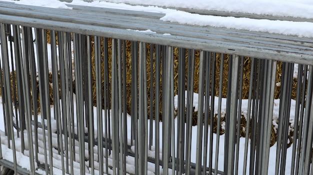 Una recinzione metallica portatile per eventi è conservata in un posto della fiera nella neve all'aperto in inverno. grate grigie per ingombrare l'area e organizzare la fila per l'evento.
