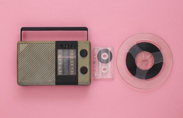 Ricevitore radio portatile, audiocassetta e bobina di nastro magnetico su rosa