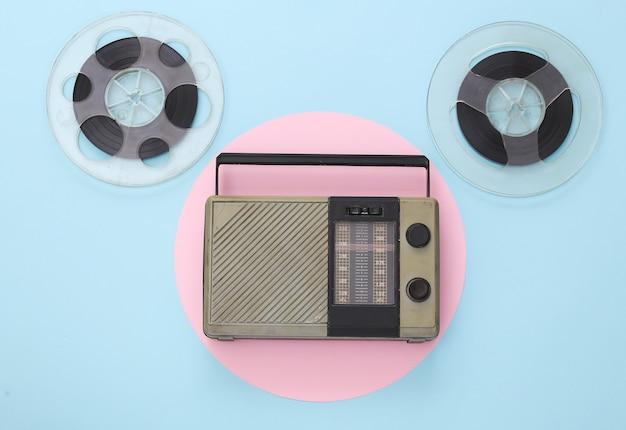Ricevitore radio portatile e bobina di nastro magnetico audio su pastello blu rosa