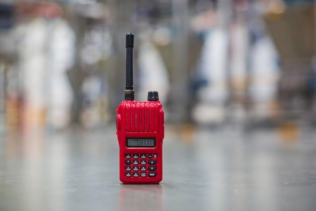 Radio portatile rossa su uno sfondo di fabbrica da pavimento