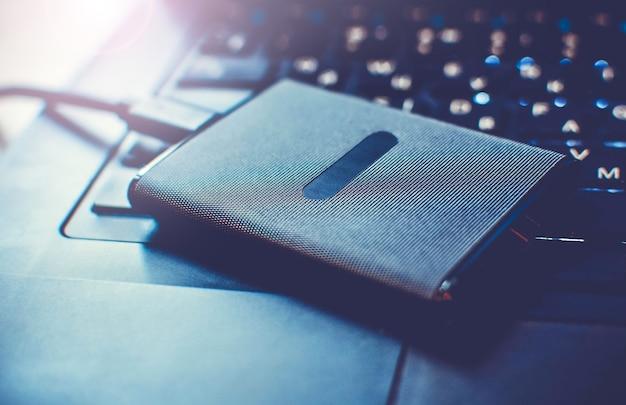 Disco rigido di unità a stato solido ssd portatile su una tastiera del laptop, da vicino