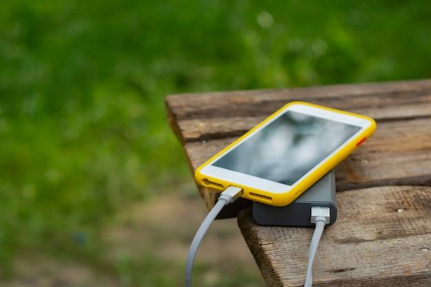 Caricabatterie portatile da viaggio. power bank carica uno smartphone su un tavolo di legno, sullo sfondo della natura. concetto sul tema del turismo.
