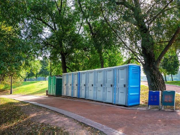 Bagni portatili in natura. lunga fila di cabine wc portatili bio nel parco di mosca. linea di wc chimici per vacanze, festival. bagno.