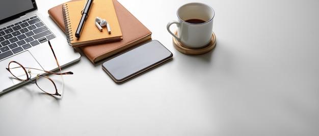 Area di lavoro portatile con copia spazio, smartphone, laptop, occhiali, tazza di caffè e articoli di cancelleria