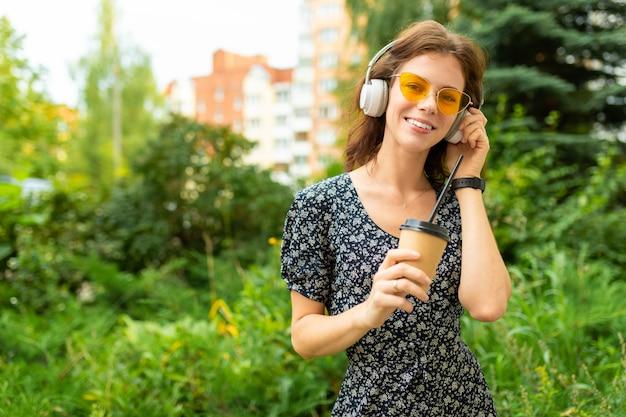 Un ritratto di giovane donna caucasica con un sorriso perfetto, labbra carnose, occhiali, auricolari, passeggiate nella natura e bevande di caffè