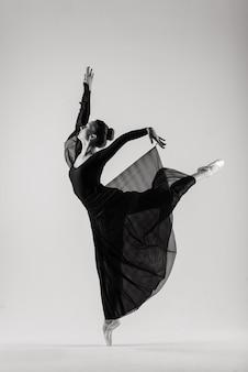 Portarit di sensuale ballerino professionista indoeuropeo callet in tuta e scarpe da punta in posa sul pavimento su bianco.