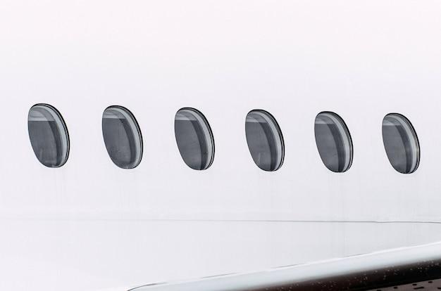 Finestre dell'oblò di un tempo umido dell'aeroplano in gocce di pioggia d'acqua, primo piano.