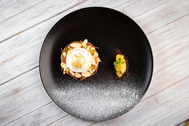 Una porzione di torta di mele con crema su un piatto nero
