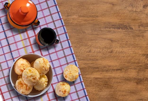 Porzione di pane al formaggio in una ciotola accompagnata da una tazza di caffè