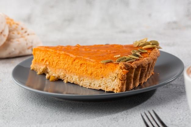 Porzione di torta aperta della zucca arancio luminosa deliziosa sul piatto grigio, decorata con i semi di zucca con il primo piano delle forcelle del dessert, vista superiore. sfondo di marmo luminoso. copia spazio. orizzontale. menu per caffè