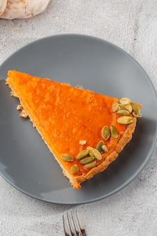 Porzione di torta aperta della zucca arancio luminosa deliziosa sul piatto grigio, decorata con i semi di zucca con il primo piano delle forcelle del dessert, vista superiore. sfondo di marmo luminoso. copia spazio. verticale. menu per caffè