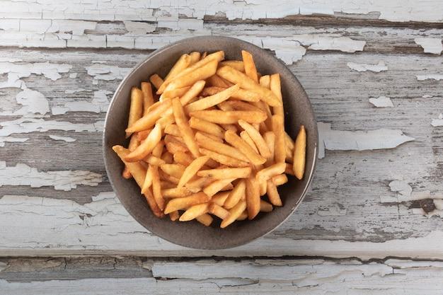 Porzione di patatine fritte nella ciotola sul tavolo rustico.