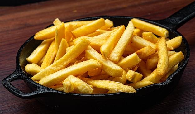 Porzione di patatine fritte servite in padella di ferro su fondo di legno