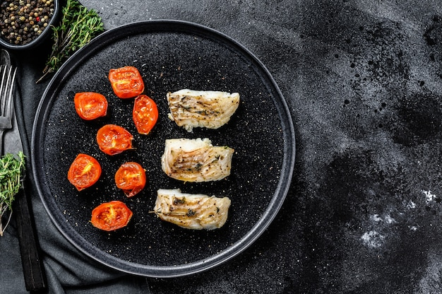 Una porzione di pollock alla griglia, al forno o filetti di pesce carbone. sfondo nero. vista dall'alto. copia spazio.