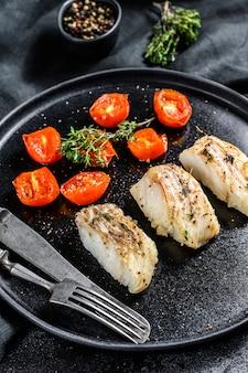 Una porzione di filetti di pollock alla griglia o al forno. sfondo nero. vista dall'alto