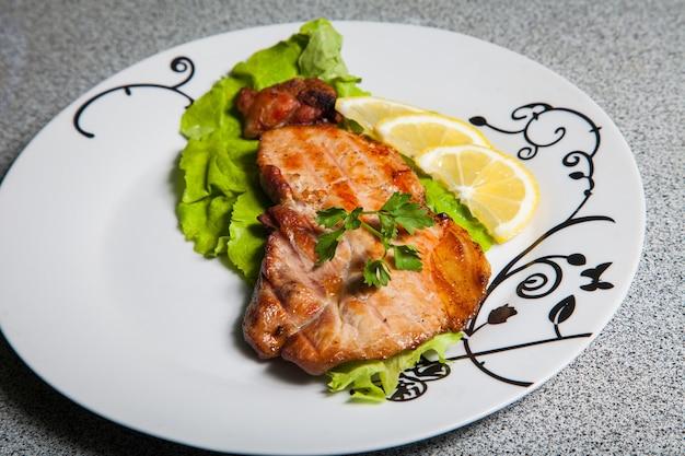 Porzione di carne alla griglia e tre parti di limone sulla piastra