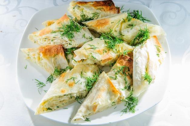 Porzione di tortilla alla griglia ripiena di formaggio e aneto servita su piatto