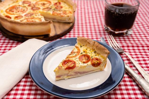 Porzione di torta di formaggio e prosciutto o quiche lorraine servita su un piatto. cibo domestico, concetto sano