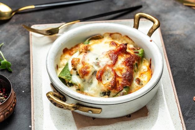 Porzione di crepes o frittelle di spinaci calde con pollo e funghi al forno con formaggio. menu del ristorante, dieta, ricetta del libro di cucina. vista dall'alto.