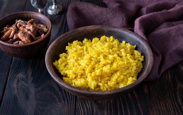 Porzione di risotto allo zafferano con finferli fritti