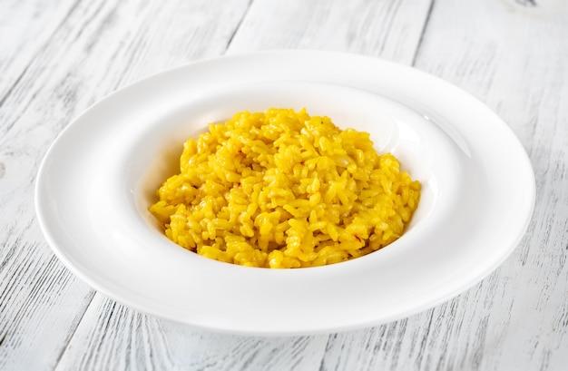Porzione di risotto allo zafferano sulla tavola di legno